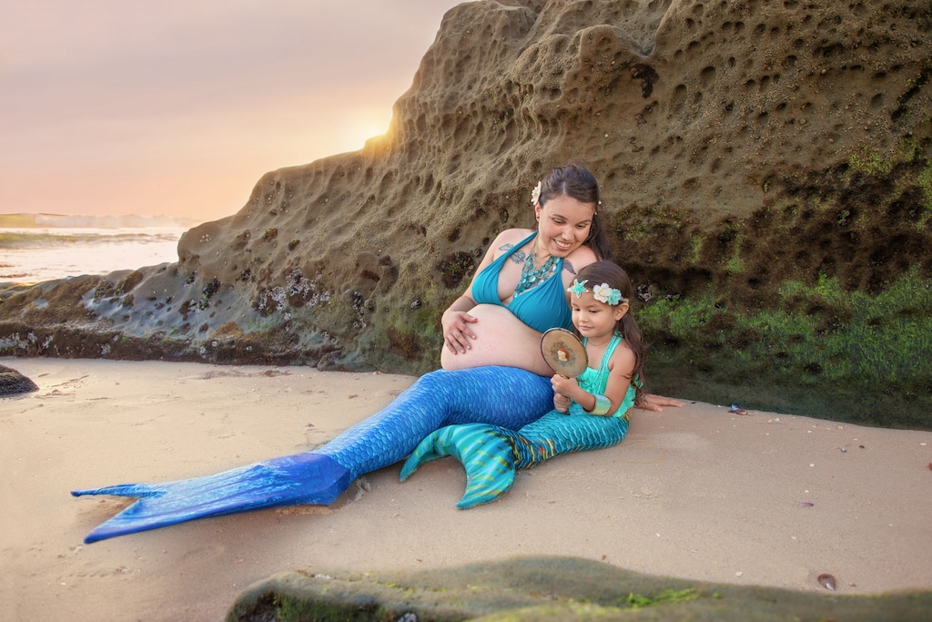 Pregnant mermaid and her daughter on a beach in San Diego