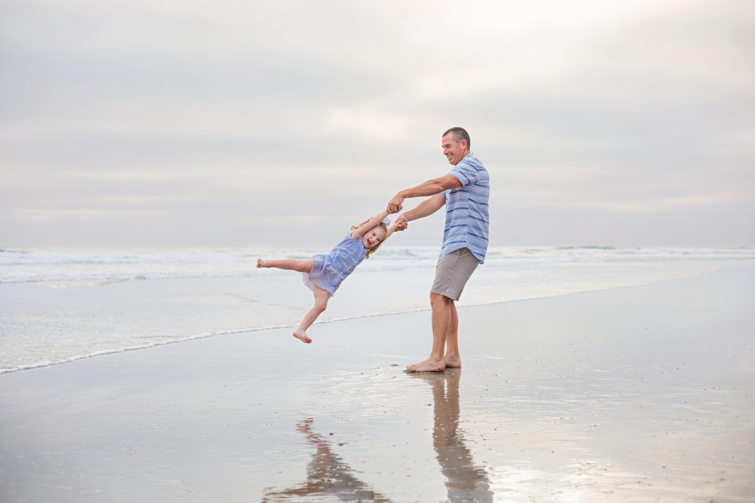 Father swinging daughter around at a San Diego beach