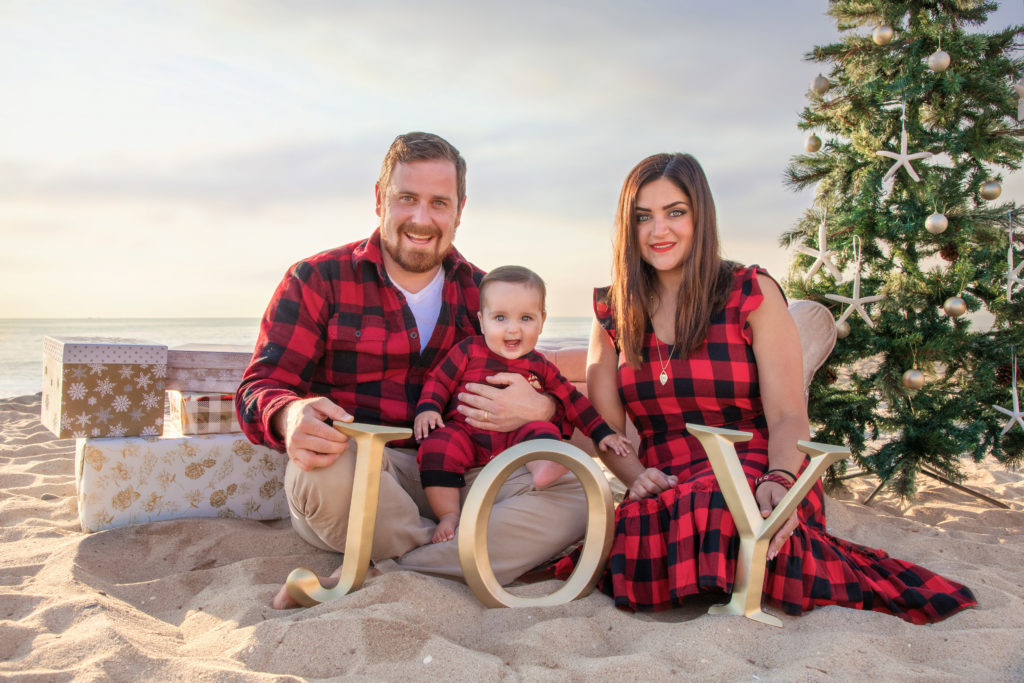 San Diego Family sitting on the beach with a Christmas tree