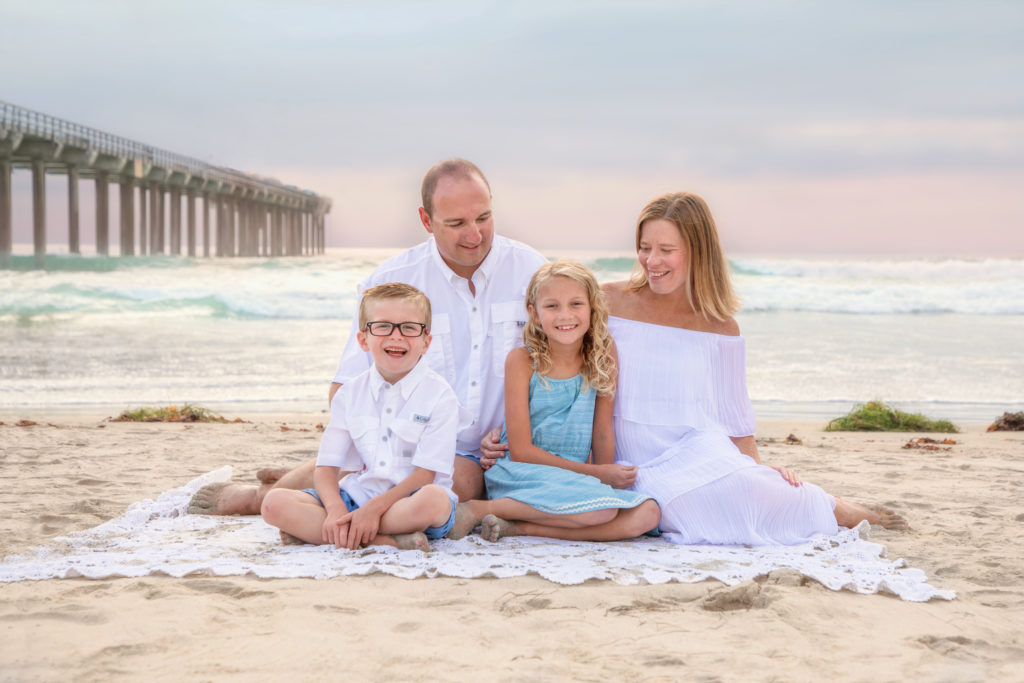 Family sitting on the beach at Scripps Pier in La Jolla