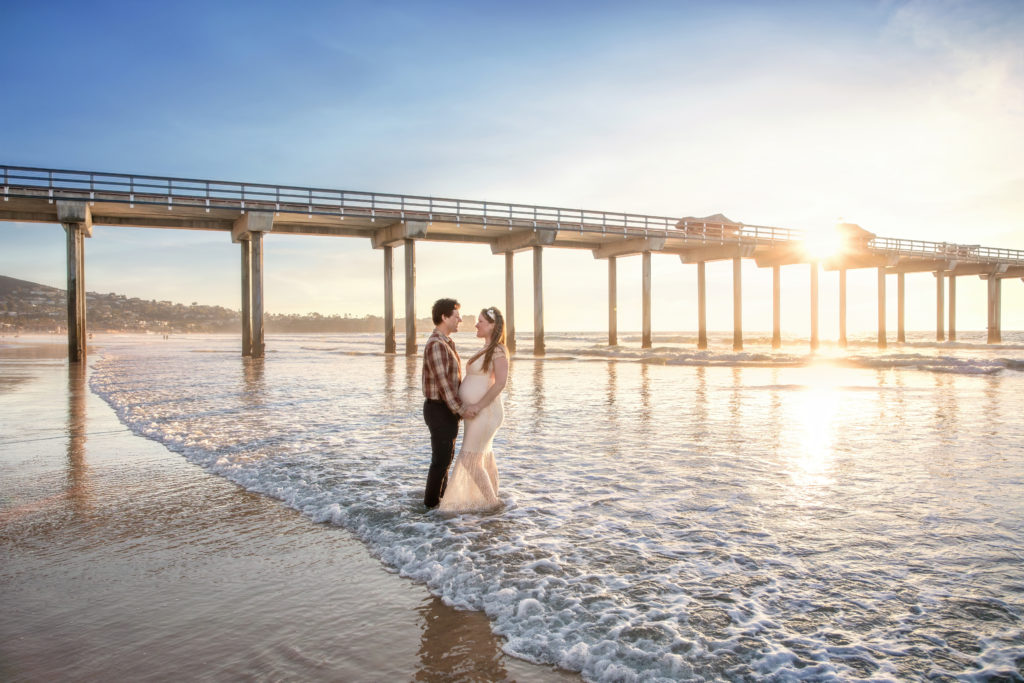 Husband and wife in the waves at Scripps Pier at sunset