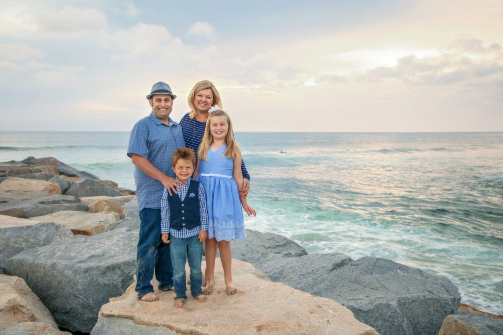 Family standing on South Ponto Beach jetty in Carlsbad