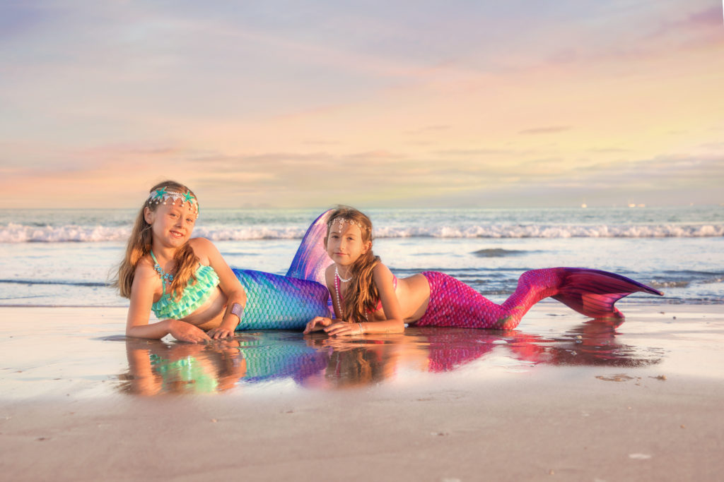 Two little pink and purple mermaids on the beachin San Diego at sunset