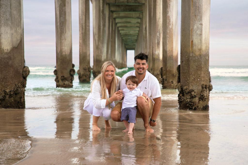 Family posing under Scripps Pier