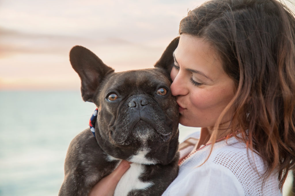 Woman kissing her French bulldog.