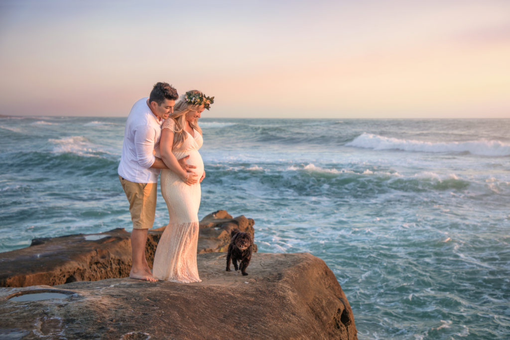 Beach maternity photo shoot with dog at sunset.
