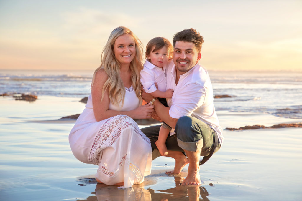 Family photo shoot with mother and father and their son on the beach.
